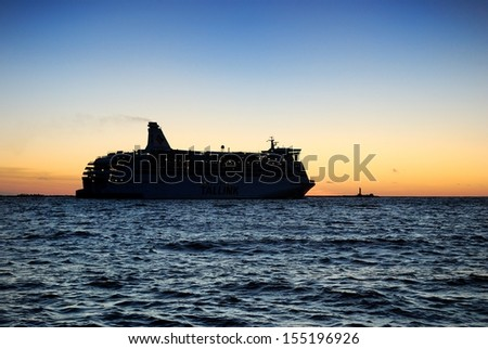 Passenger ferry leaving port at a colorful sunset