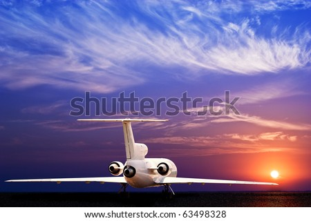Passenger jet airliner on ground and stunning sunset - stock photo