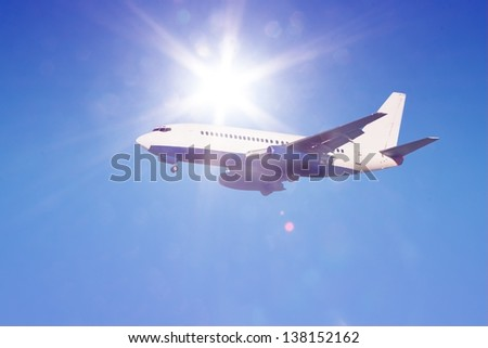 passenger jet in flight against clear blue sky with sun rays and flares landing gear down