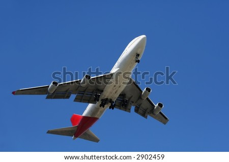 Passenger jet in flight, viewed from below, against a clear blue sky.