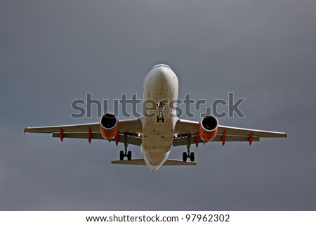 Passenger jet landing at airport, against a grey sky. - stock photo