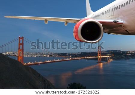 Passenger Jet Plane Flying above the Golden Gate Bridge for travel concept - stock photo
