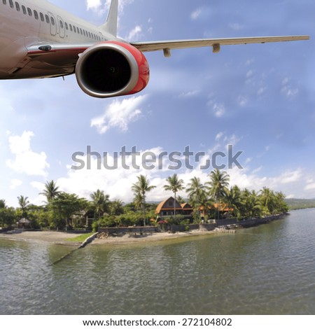 Passenger Jet Plane Flying Above tropical Island for travel concept - stock photo