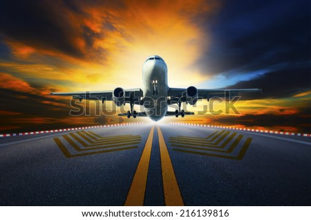 passenger jet plane preparing to take off from airport runways with motion blur against beautiful dusky sky - stock photo