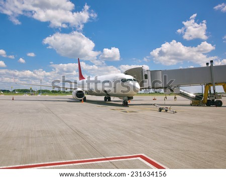 Passenger jet plane standing at the terminal gate - stock photo