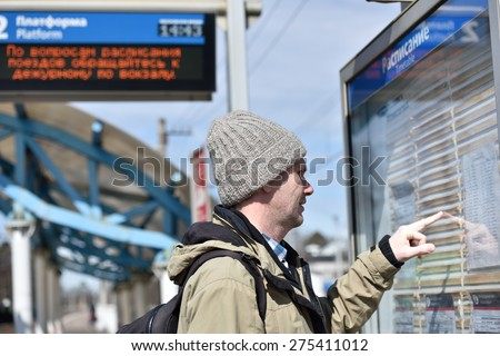 Passenger looking at timetable on a Russian commuter train station - stock photo