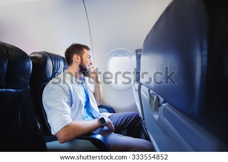 passenger of airplane talking on mobile phone - stock photo