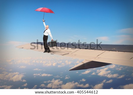 Passenger or pilot with umbrella balancing on airliner wing. Travel insurance concept. Funny situation from travel. - stock photo