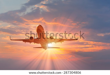 passenger plane fly down over take-off at sunset - stock photo