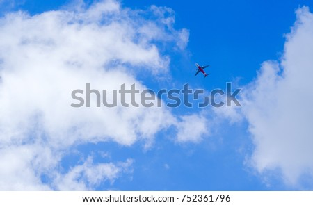 Passenger plane in white clouds and blue sky