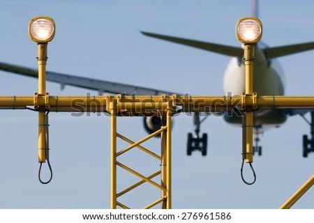 Passenger plane is decending towards the runway behind the runway light. - stock photo