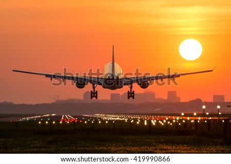 Passenger plane is landing during a wonderful sunrise. - stock photo