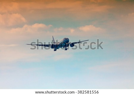 Passenger plane takes off at sunset sky background