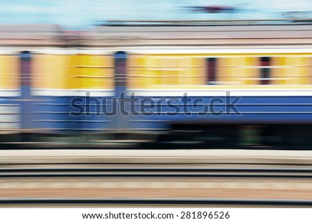 Passenger train passing quickly past the station at a speed on a sunny day - stock photo