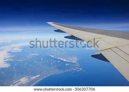 Passenger view from airplane flying over ocean and island - stock photo