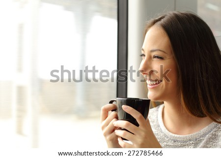 Passenger woman drinking coffee during a train travel and looking through the window - stock photo