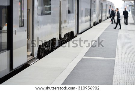 Passengers and commuter train - stock photo