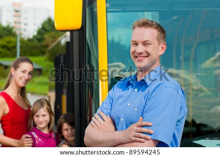 Passengers boarding a bus at a bus station; in the foreground a bus driver to be seen - stock photo