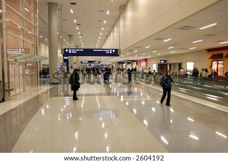 Passengers in modern airport (recognizable faces are blurred) - stock photo