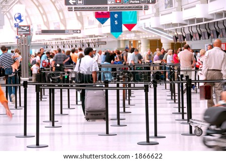 Passengers lining up at check-in counter at the modern international airport, no faces visible - stock photo