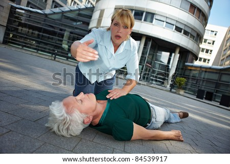 Passerby with unconscious senior woman asking for First Aid help - stock photo