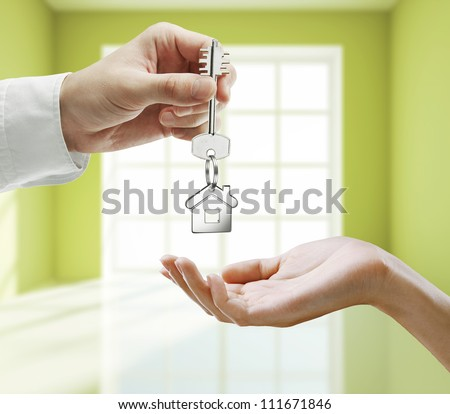 passing key against backdrop of green room - stock photo
