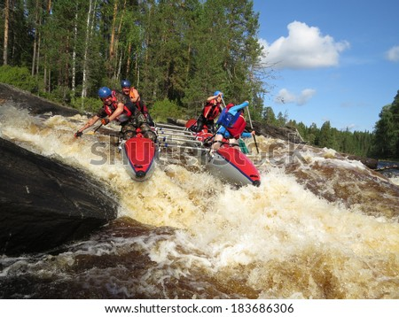 passing of rough river falls by team of people on an inflatable catamaran - stock photo