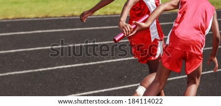 Passing the baton in a relay race - stock photo