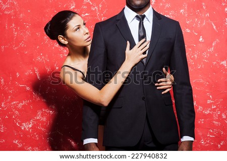 Passion and desire. Cropped image of man in formalwear standing against red background while woman embracing him from behind - stock photo