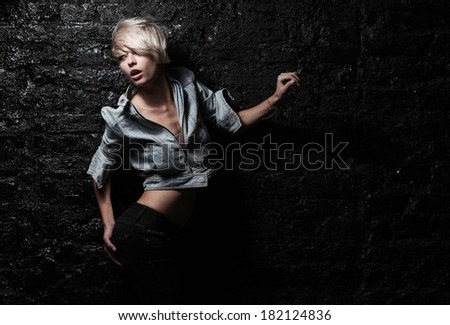 Passion beauty blond woman near black brick wall - stock photo