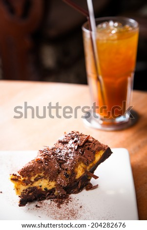 Passion cake and chocolate on top with glass of tea - stock photo