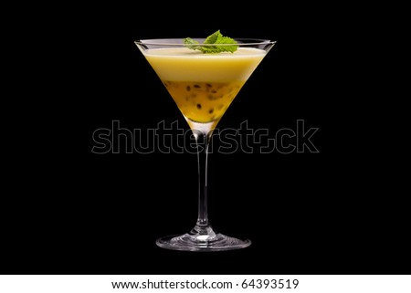Passion fruit, and lemon jello pudding in martini glass with mint sprig on black background.