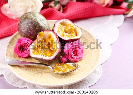 Passion fruit on plate on color wooden background - stock photo