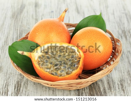 Passion fruits in wicker basket on table close-up - stock photo