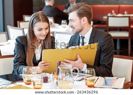 Passionate about business. Young smiling business manager smiles to his female colleague while they look through the business papers during the lunch - stock photo