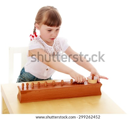 Passionate about the little blonde girl with short bangs and long braids white t-shirt with short sleeves sits at his Desk, intently studying Montessori material girl with her friends would be going - stock photo