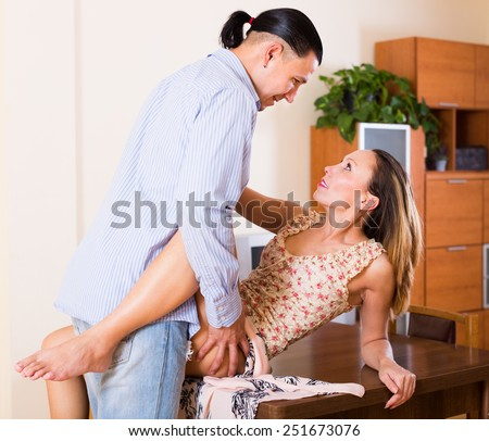 Passionate adult couple of lovers having sex on the table at home - stock photo