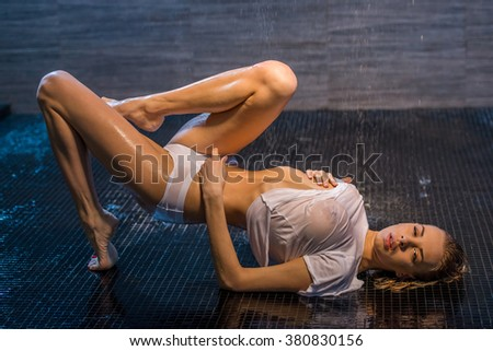 Passionate beautiful young woman enjoying pleasant shower, lying on the floor in wet panties and t-shirt and looking at camera - stock photo