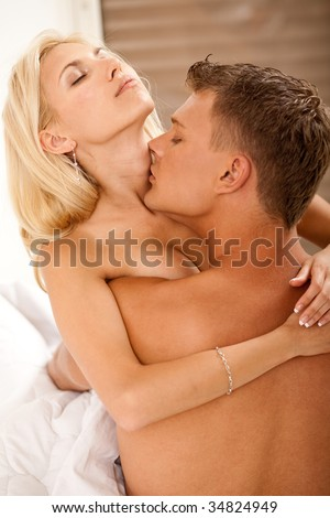 Passionate couple enjoying in bed - stock photo