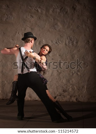 Passionate dancers performing tango style in urban setting - stock photo