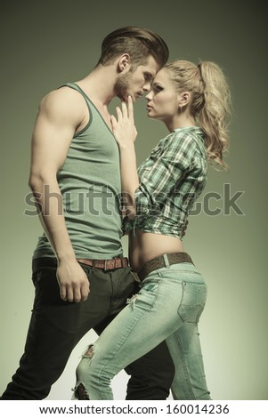 passionate fashion couple standing embraced and looking at each other - stock photo
