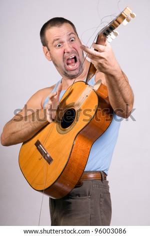 passionate guitarist with broken guitar - stock photo