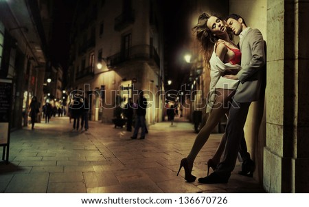Passionate lovers over night city background - stock photo