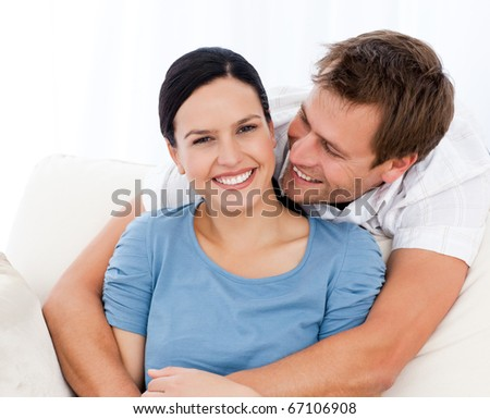 Passionate man hugging his girlfriend while relaxing on the sofa at home - stock photo