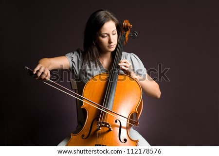 Passionate real artist, young woman playing her classical instrument. - stock photo