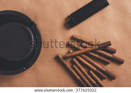 Passionate smoker flat lay top view arrangement, warm retro toned image of ashtray, cigarettes and a lighter - stock photo
