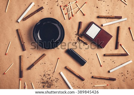 Passionate smoker flat lay top view arrangement, warm retro toned image of ashtray, matches, lighter and cigarettes scattered across the table. - stock photo