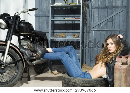 Passionate tempting cute girl in black leather jacket and blue jeans lying on the floor in garage interior on grey wooden wall background, horizontal picture - stock photo