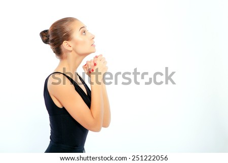 Passionate to dance. Side view portrait of beautiful elegant woman in black ballet dress clasping her hands in awe while standing isolated on white background - stock photo