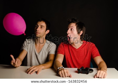 Passionate video gamer discovering a balloon, a concept - stock photo